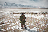 Jaffar, brother of Sufi, recently lost his wife. He is the shepherd for the camp, taking the herd out in extreme cold..In and around the camp of Ortobil, Manara (Sufi camp), near the borders with China and Tajikistan..Trekking with yak caravan through the Little Pamir where the Afghan Kyrgyz community live all year, on the borders of China, Tajikistan and Pakistan.