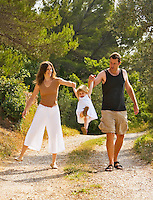 Couple play with their 28 month old daughter while walking down a country track. Model released.