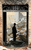 Photographer: Rick Findler..06.10.12 A young boy peers through the remains of a doorway amongst rubel caused by heavy shelling in the city of Aleppo, Syria.