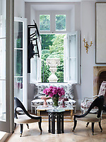 In the family room the atmosphere is light, cool and relaxed achieved by the use of neutral colours and natural materials. Antique pieces mix easily with more modern additions. A corner by an open window provides a sitting room area in miniature.