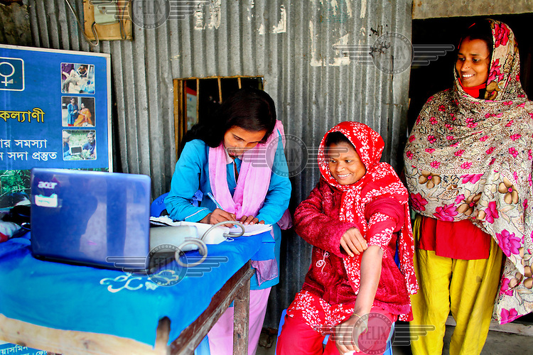 After walking three Kilometres Beauty Begum (28) comes to the house of Info Lady Jeyasmin. She had been feeling unwell for several months and was told by a village healer that she was diabetic and that the fees for treatment would be about 1700 Taka (13 GBP). After testing her for diabetes she found that Beauty was no diabetic and recommeded she seek the advice of a proper doctor to see why she was unwell. She charged 50 Taka (.40 GBP) for this service. In rural Bangladesh the Info Ladies are bringing internet services to men and women who need information but don't have the means to access the web. After three months of training the Info Ladies set out each day in their pink and blue uniforms to cycle to remote villages where they provide Skype connections to villagers who want to communicate with relatives working overseas. They also provide tech services, photographs, health tests, cosmetics and other small items that can be easily carried.