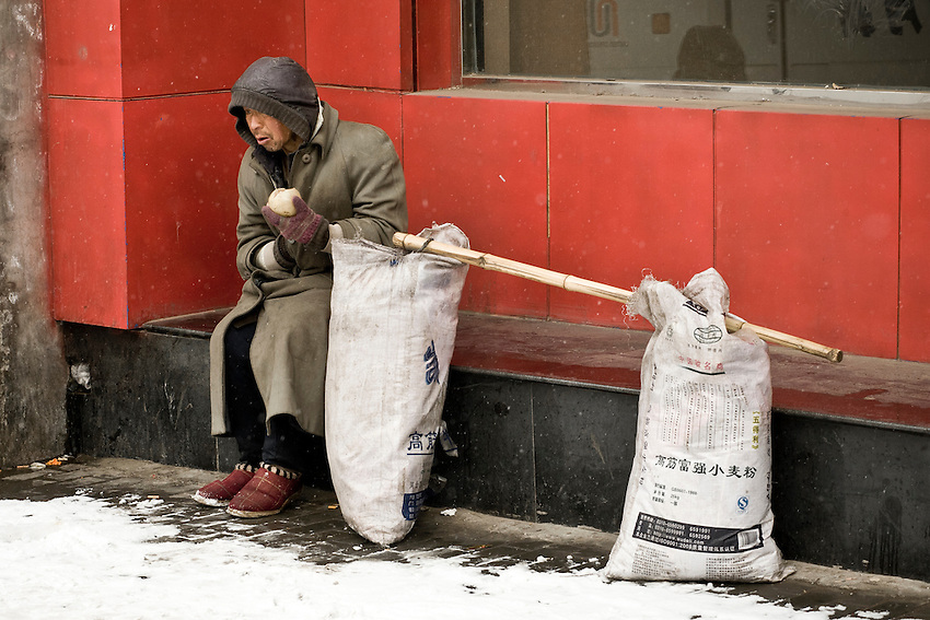 A man is eating an apple near the Forbidden city after he had slept in the street  after a snowfall that local authorities say they have artifically provoked to fight the exceptional drought in northern China.