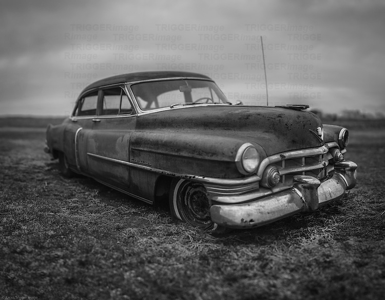 Classic Cadillac car from 1960's rusting in a field