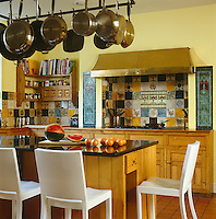 The yellow-painted country-style kitchen has pine units and a splashback of multi-coloured tiles around the walls