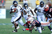 30 October 2010:  FIU running back Kedrick Rhodes (9) evades Florida Atlantic linebacker Randell Johnson (15) while carrying the ball in the first quarter as the Florida Atlantic University Owls defeated the FIU Golden Panthers, 21-9, at Lockhart Stadium in Fort Lauderdale, Florida.