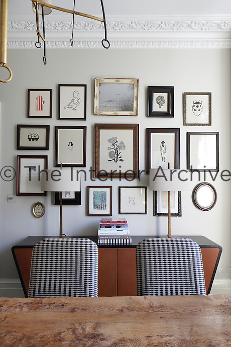 A collection of framed drawings displayed above a retro sideboard in the dining room