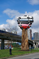 A man photographing a new public art installation entitled Trans Am Totem in Vancouver, British Columbia. This playful sculpture created by Vancouver artist Marcus Bowcott consists of five recycled cars placed on top of the trunk of an old-growth cedar tree.