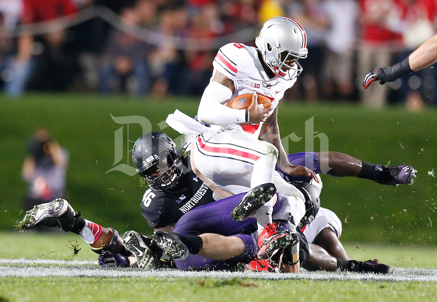 Ohio State Buckeyes quarterback Braxton Miller (5) is tackled by Northwestern Wildcats linebacker Collin Ellis (45) during Saturday's NCAA Division I football game at Ryan Field in Evanston on October 5 2013. (Barbara J. Perenic/The Columbus Dispatch)
