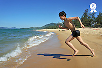 Boy (12) running into water on beach (Licence this image exclusively with Getty: http://www.gettyimages.com/detail/83154200 )