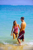 A couple enjoys the aqua water and warm sun at Lanikai Beach near Kailua, on Oahu's Windward side.