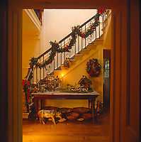Festive green and red garlands, hang from the baluster above the elaborate nativity scene laid out on the hall table