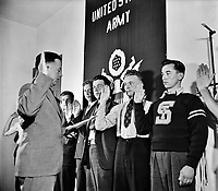 Group of men being sworn in by Major Seth Gayle, Jr. in Washington, D.C., 1940.<br /> <br /> Photo by Harris & Ewing.