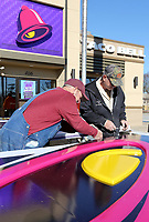 NWA Democrat-Gazette/DAVID GOTTSCHALK Ronnie Owens (left), and Jack Owens, with R & O Sign Company of Fort Smith, trim Thursday, March 21, 2019, the edges of a facade for a new double sided sign at the Taco Bell restaurant in Springdale. The installation of the new facade included converting 400 watt Metal Halide lights to light-emitting diodes in the sign.