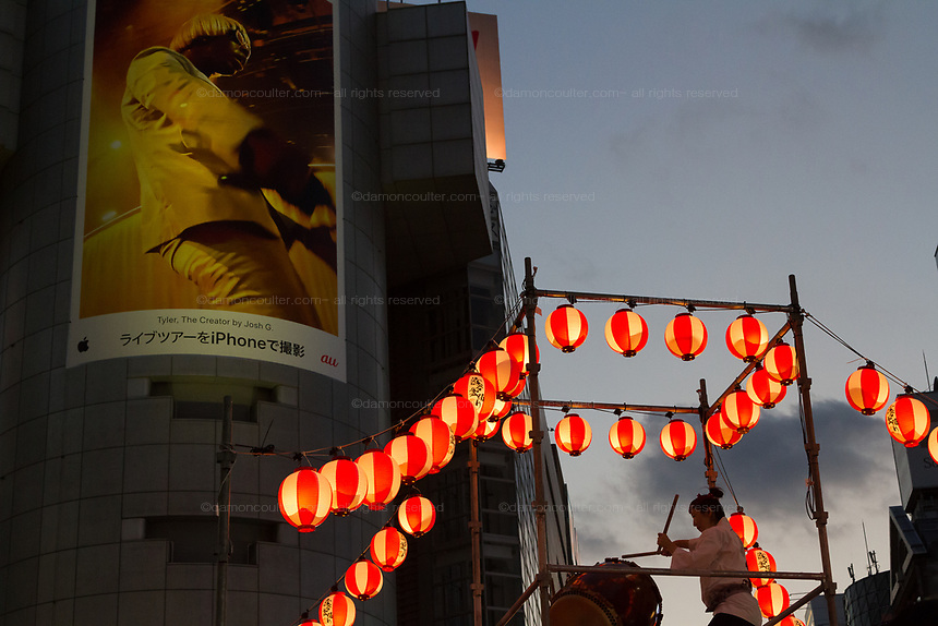 A Taiko drummer on a platform called a yagura  during  the third Annual Shibuya Bon Odori festival, Bon dancing is a Japanese custom at summer matsuri or festivals all over Japan. The Shibuya Bon Odori takes place in front of the iconic Shibuya 109 building. Shibuya, Tokyo, Japan. Sunday August 4th 2019