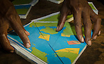 A Lobo Village community member prepares a puzzle from a map of Triton Bay no-take zones designated by local communities.