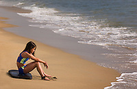 Girl (9-10) sits on her surfboard waiting for waves at he beach.