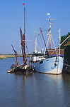 AT5BRB Sailing barge and boat moored quayside Snape maltings Suffolk England
