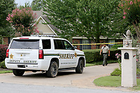 NWA Democrat-Gazette/DAVID GOTTSCHALK  A member of the Washington County Sheriff's Department walks down the driveway Friday, July 14, 2017, at 2905 Rom Orchard Road. Deputies are investigating a reported stabbing at the residence just east of Fayetteville. The stabbing was reported at 5:48p.m. Thursday.