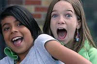 Two girls react to being photographed on a school playfield.