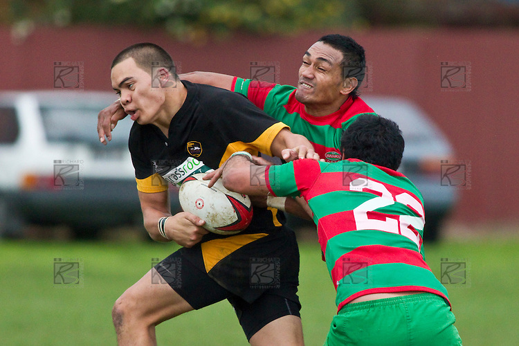 Robert Wallis trie to keep hold of the ball as he is tackled by Ray Taupo and Sio Petelo. Counties Manukau Premier Club Rugby game between Waiuku and Bombay, played at Waiuku on Saturday July 5th 2010. Waiuku won 59 - 14 after trailing 12 - 14 at halftme.