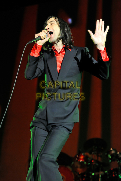 PRIMAL SCREAM - BOBBY GILLESPIE.Performing live in concert to celebrate the 20th Anniversary of the band's classic album 'Screamadelica' at Olympia Exhibition Centre, London, England, UK, November 27th, 2010..on stage music gig band half length black red shirt suit microphone singing jacket hand 3/4 .CAP/MAR.© Martin Harris/Capital Pictures.