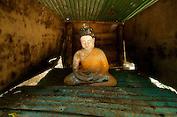 Buddha statue in a small corrugated iron structure in Phnom Kulen, Cambodia