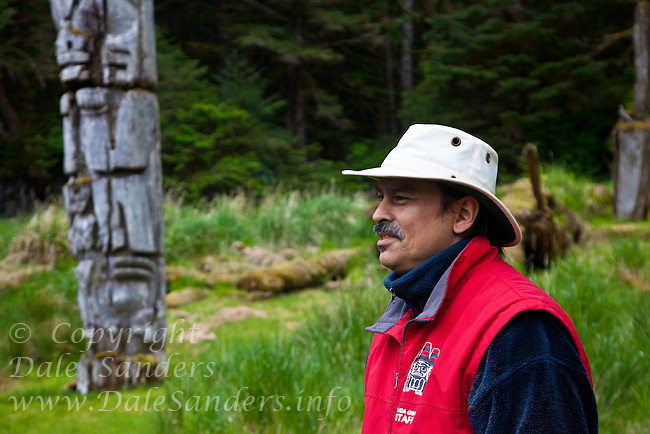 Haida Watchman - NO MODEL RELEASE - and totem poles at the long abandoned Haida village of SGang Gwaay or Ninstints, a UNESCO World Heritage Site in Gwaii Hanaas National Park on the islands of Haida Gwaii ( formerly Queen Charlotte Islands ), British Columbia, Canada.