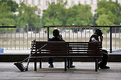 Two men, one a street cleaner taking a break from work, speak on mobile phones while sitting on a bench on the South Bank, London.