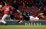 BOSTON, MA - APRIL 17: UMass' Luke Oliphant, right, scores on a passed ball under Harvard's James Kirkpatrick in the seventh inning during the 30th Annual Baseball Beanpot Championship Game at Fenway Park in Boston, Massachusetts on April 17, 2019. Photo by Christopher Evans