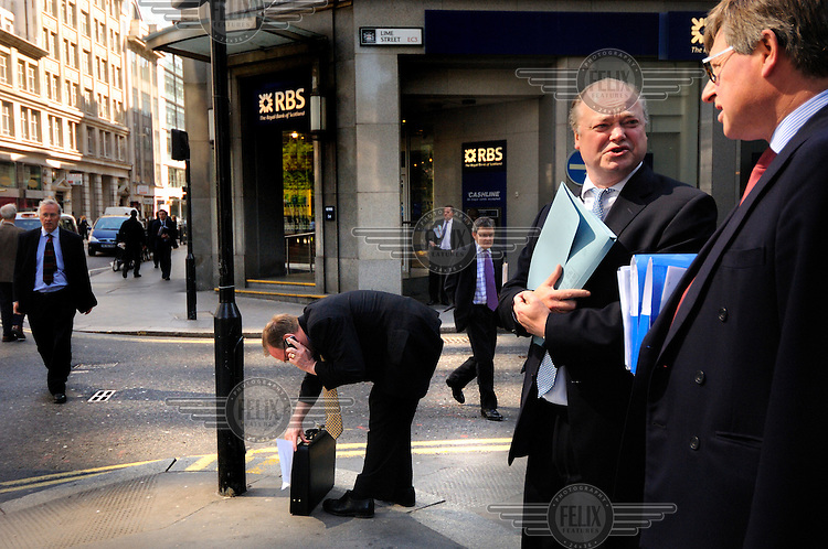 Businessmen in the City of London, next to a branch of the Royal Bank of Scotland.