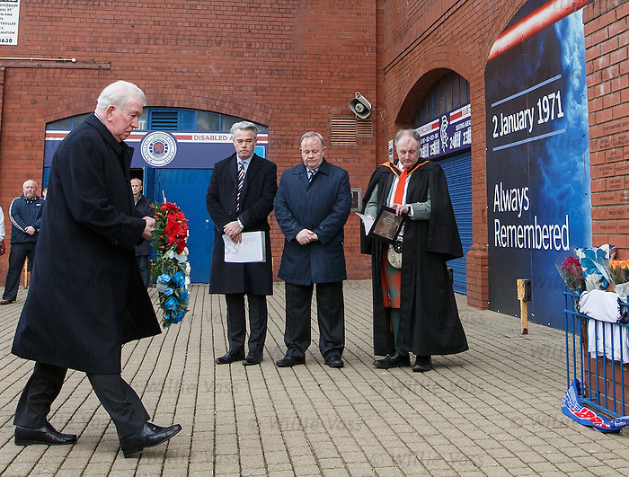 John Greig walks up to lay a wreath at the memorial statue at Ibrox Stadium