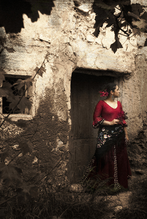 A young Spanish woman wearing traditional Flamenco dress standing in a doorway to an old  building