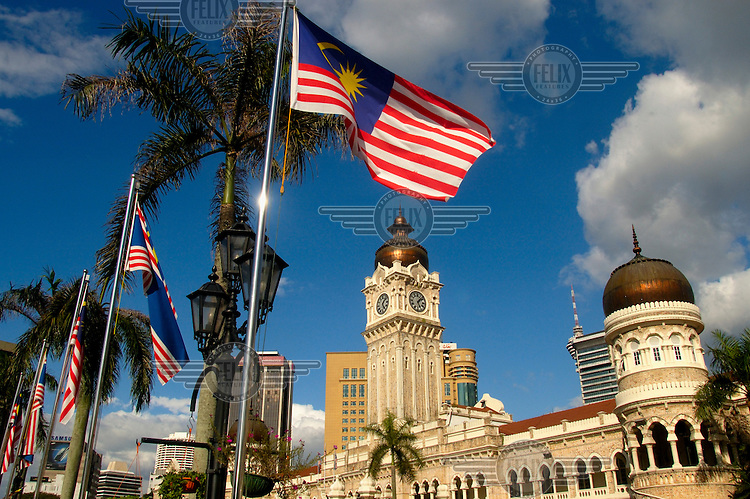 Malaysian national flag flying in front of colonial era architecture of the Sultan Abdul Samad Building on Merdaka Square downtown.