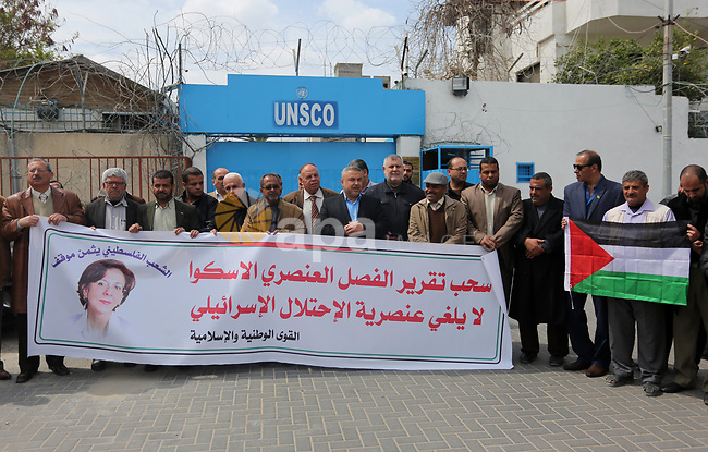 "Palestinians hold banners during a protest against the U.N. Secretary-General Antonio Guterres decision to remove Israeli 'apartheid' report from Economic and Social Commission for Western Asia (ESCWA) website, in front of the headquarter United Nation ""UNSCO"", in Gaza city on March 21, 2017. U.N. Under-Secretary General and ESCWA Executive Secretary Rima Khalaf resigned after saying she was pressured to withdraw a controversial report that accused Israel of establishing an ""apartheid state."". Photo by Ashraf Amra"