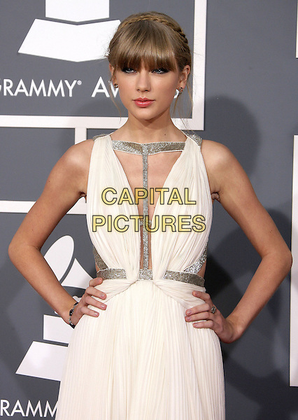 Taylor Swift.The 55th Annual GRAMMY Awards held at STAPLES Center, Los Angeles, California, USA..February 10th, 2013.grammys half length white silver gold straps dress hands on hips fringe bangs hair cut out away pleats pleated    .CAP/ADM.©AdMedia/Capital Pictures.