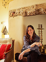 Monica Vinader pictured sitting in the large inglenook fireplace of the family room of her Norfolk house