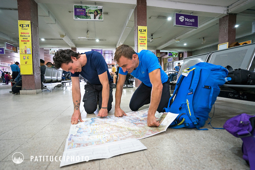 Ueli Steck and Colin Haley looking at a map in the Kathmandu airport while discussing plans for their climbing expedition to Nuptse, Nepal.
