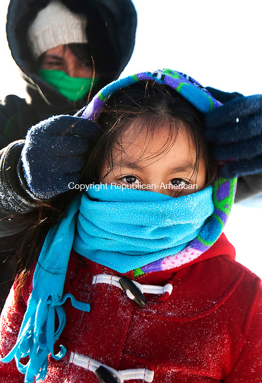 WATERBURY,  CT-021515JS03- Shilyia Zhiazlprn , 7, of Waterbury gets help bundling up from the cold by Estefany Maldonado while sledding at Fulton Park in Waterbury on Sunday. The bitter cold temperatures are in the precast through the middle of the week. <br /> Jim Shannon Republican-American