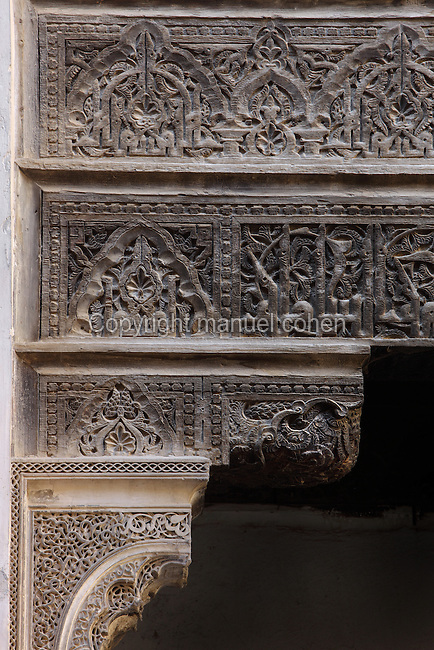 Detail of carved wooden panels around archway, Sahrij Medersa, (Medersa des Andalous), 1321, Fez, Medersa Sahrij, Fez, Morocco, pictured on February 23, 2009 in the morning. The Sahrij Medersa takes its name from the pool in its courtyard, (sahrij means basin). Green and white minarets crown the theological school founded by Merinid sultan Abou al-Hassan and attached to the Al-Andalous mosque.  It is decorated with ornate  dark cedar panels (mashrabiya), decorated tiles (zellij), marble pavings and intricate plasterwork. Fez, Morocco's second largest city, and one of the four imperial cities, was founded in 789 by Idris I on the banks of the River Fez. The oldest university in the world is here and the city is still the Moroccan cultural and spiritual centre. Fez has three sectors: the oldest part, the walled city of Fes-el-Bali, houses Morocco's largest medina and is a UNESCO World Heritage Site;  Fes-el-Jedid was founded in 1244 as a new capital by the Merenid dynasty, and contains the Mellah, or Jewish quarter; Ville Nouvelle was built by the French who took over most of Morocco in 1912 and transferred the capital to Rabat. Picture by Manuel Cohen.