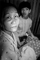 Kroong / Distretto Sa-Thai / Kontum / Vietnam.<br /> All'interno di una casa molto povera, una baracca ai margini del villaggio, vive Nguyen Tan Cuong di 16 anni, affetto dalle gravi conseguenze della sindrome da diossina.La madre Bui Thi KimThong, di 58 anni, dice che tiene il figlio in gabbia per salvaguardarne l'incolumità. Non sa come gestire la situazione e non sa nemmeno che a Saigon e Hanoi ci sono centri specializzati per la cura di bambini come lui.<br /> Kim Thong nel dopoguerra ha avuto 11 figli, tutti affetti dalla sindrome da diossina. Tre sono nati morti, altri tre sono deceduti subito dopo la nascita. Tan Cuong è il più grave. Per questa come le altre famiglie che vivono di agricoltura è una tragedia senza fine che unisce il dolore alla povertà.<br /> Foto Livio Senigalliesi.<br /> Kroong / Sa-Thai district / Kontum Province / Vietnam<br /> Consequenses of the war in Vietnam 40 years later.Nguyen Tan Cuong (16) is heavy affected by dioxine syndrome. His mather, Bui Thi KimThong, put him in a wooden cage. Poverty ignorance and trauma produced untold sufferings.<br /> Photo Livio Senigalliesi.