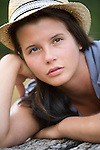 A young woman wears a straw hat outdoors.