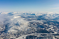 Aerial view of arctic landscape, frozen river and the Lyngen Alps from aircraft approaching Tromso in the Arctic Circle in Northern Norway