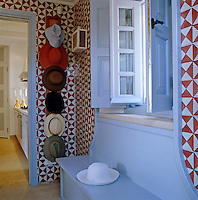 The wall of the passage which leads to the kitchen is lined with hand-painted red and white Italian tiles and a further selection of hats