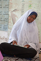 Jambiani, Zanzibar, Tanzania.  African Muslim Primary school teacher.  The teacher sits on the floor, as do the students, since the school has no furniture.