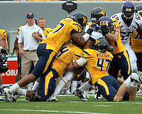 The WVU defense gang tackles an East Carolina running back. The WVU Mountaineers defeated the East Carolina Pirates 35-20 at Mountaineer Field at Milan Puskar Stadium, Morgantown, West Virginia on September 12, 2009.