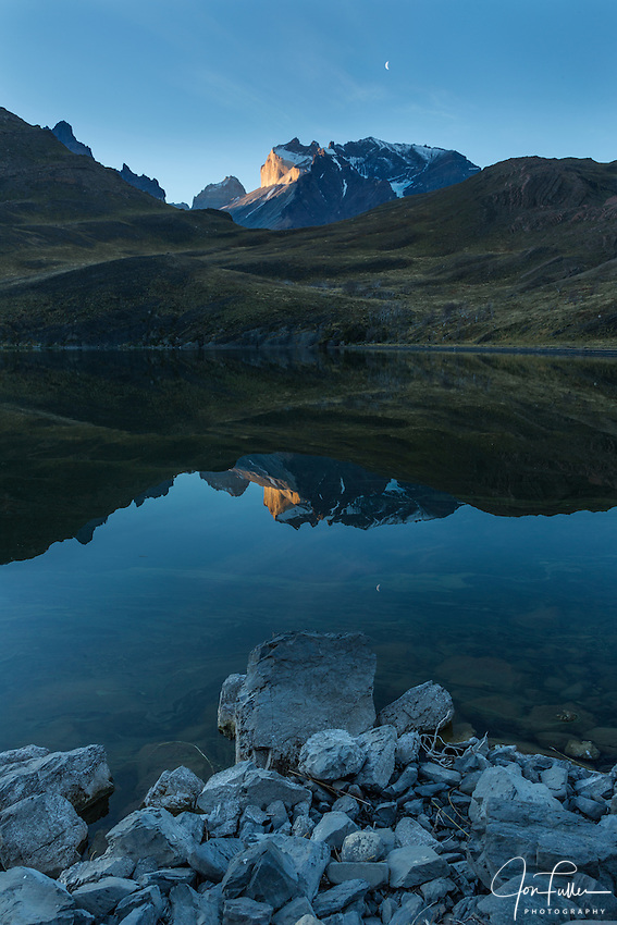 Sunset light on the face of Monte Almirante Nieto reflected in Laguna Melliza.  Just to the left is the top of Torre Sur, or the South Tower, of the Torres del Paine.  The crescent moon is in the sky above.  Torres del Paine National Park in Patagonia, Chile.  A UNESCO World Biosphere Reserve