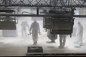 Duisburg, Germany, 14 August 2014. Pictured: workers clearing up the area after the performance. Dress rehearsal of Le Sacre du Printemps conceived and directed by Romeo Castellucci. Choreography for 40 machines spraying bonemeal or bone dust behind a plexi-glass screen set to music by Igor Stravinsky, at Geblaesehalle in Landschaftspark Duisburg-Nord. Le Sacre du Printemps (the rite of spring) is part of Ruhrtriennale, International Festival of the Arts, North Rhine-Westphalia, Germany. Photo: Bettina Strenske