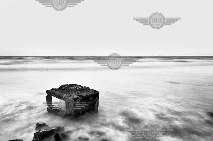 The remanant of a concrete defensive structure are visible on a rocky beach in France along the route of the Atlantic Wall (Atlantikwall in German).The Atlantic Wall (or Atlantikwall in German) was a system of defensive structures built by Nazi Germany between 1942 and 1945, stretching over 1,670 miles (2,690 km) along the coast from the North of Norway to the border between France and Spain at the Pyrenees. The wall was intended to repulse an Allied attack on Nazi-occupied Europe and the largest concentration of structures was along the French coast since an invasion from Great Britain was assumed to be most likely. Slave labour and locals paid a minimum wage were drafted in to supply much of the labour. There are still thousands of ruined structures along the Atlantic coast in all countries where the wall stood except for Germany, where the bunkers were completely dismantled.