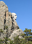 President George Washington  shown in side view at Rushmore National Memorial which is a sculpture carved into the granite face of Mount Rushmore near Keystone South Dakota.  Mt. Rushmore Sculpted by Gutzon Borglum and later his son Lincoln Borglum, Mount Rushmore features 60 foot sculptures of the heads of former United States presidents, George Washington, Thomas Jefferson, Theodore Roosevelt and Abraham Lincoln.  South Dakota historian Doane Robinson is credited with conceiving the idea of carving the likenesses of famous people into the Black Hills region of South Dakota..