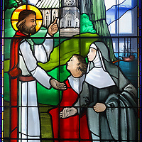 Marie de L'Incarnation's vision of Christ, stained glass window, 1972, in the funerary chapel of the Chapelle des Ursulines, Quebec City, Quebec, Canada. Marie of the Incarnation, 1599-1672, is depicted with Madame de la Peltrie listening to Christ, who tells her to go from France to Canada on a mission. The Ursuline Convent was founded in 1639 and is the oldest girls' school on the continent. The building now houses a museum, the Musee des Ursulines de Quebec. The Historic District of Old Quebec is listed as a UNESCO World Heritage Site. Picture by Manuel Cohen